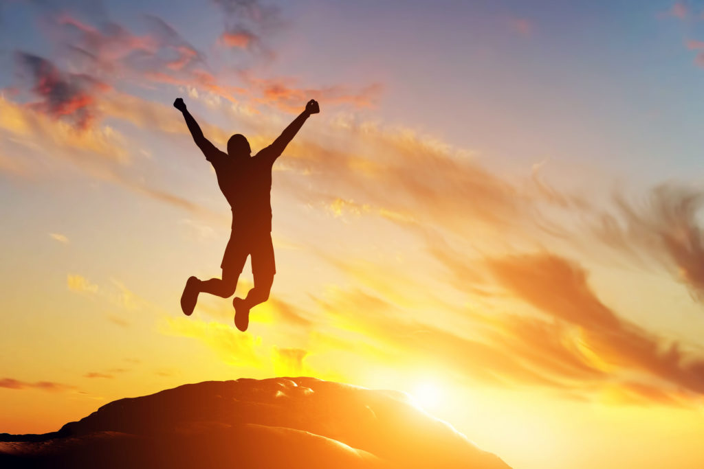 31476914 - happy man jumping for joy on the peak of the mountain, cliff at sunset. success, winner, happiness